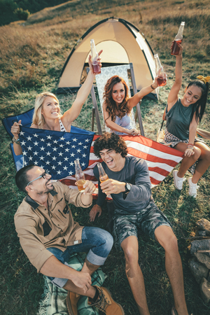 Happy young friends Fourth of July celebration and enjoy a sunny day at the mountain. Theyre holding american flag, laughing and toasting with beer bottles near tent.