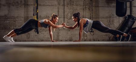 Zwei junge muskulöse Mädchen, die Plankenübung am Cross-Fit-Training machen.