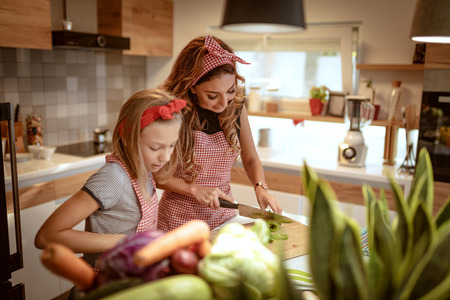 Cute little girl and her beautiful mom are cutting vegetables and smiling while cooking in kitchen at home.