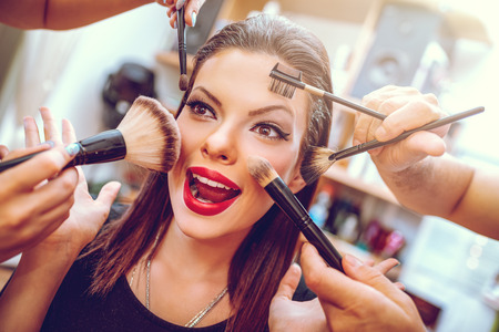 Portrait of a pretty pin-up girl getting make-up applied by a makeup with many  hands. Close-up. Stock fotó