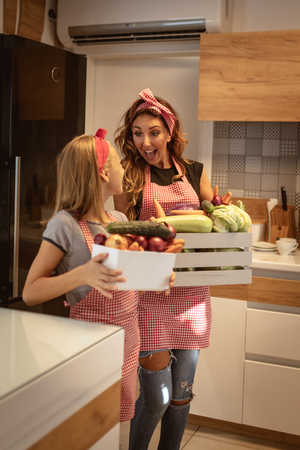 Mother and daughter bring crates full of vegetables into kitchen preparing to cook.