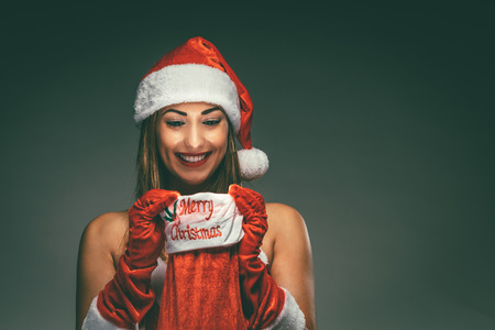 Cheerful beautiful young woman in Santa Claus costume enjoying and surprisingly looking what is inside of a red christmas stocking. Фото со стока