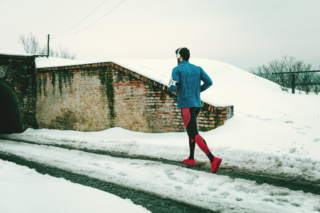 A male runner with headphones on his ears running in the public place during the winter training outside in. Copy space.