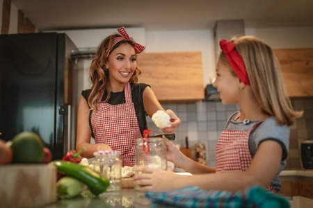 Happy mother and her daughter enjoy preparing for marinating cauliflower and making healthy meal together at their home kitchen.