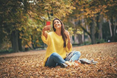 Retrato de una bella mujer sonriente tomando selfie en bosque en otoño.