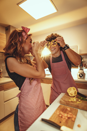 Happy young couple enjoys and having fun in making and having healthy meal together at their home kitchen.