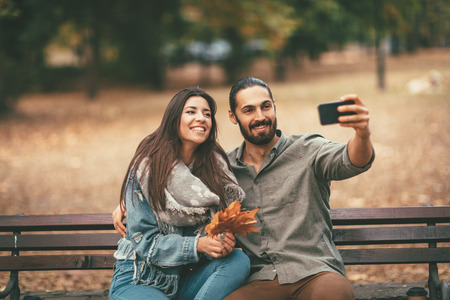Beautiful smiling couple enjoying in sunny city park in autumn colors looking each other. They are sitting on the bench and having fun with smarthphone taking selfie.