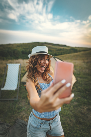 Happy young woman enjoys a nice day in nature. Shes smiling and taking selfie with smartphone.