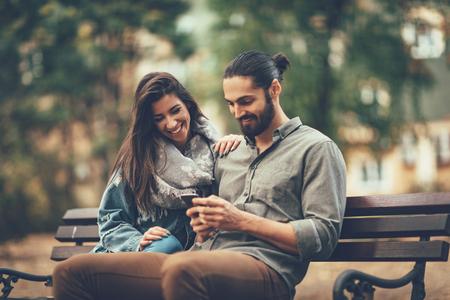 Hermosa pareja sonriente disfrutando en el soleado parque de la ciudad en colores otoñales mirando el uno al otro. Están sentados en el banco y se divierten con teléfonos inteligentes. Foto de archivo