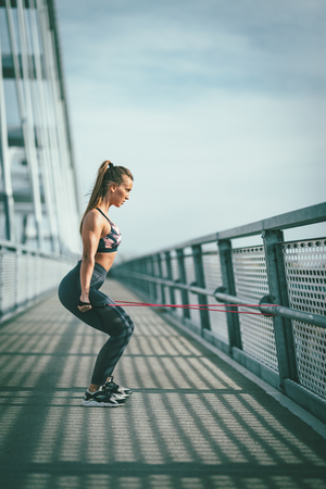 Muscular young woman is doing strong fit body training with elastic rubber band on the bridge.