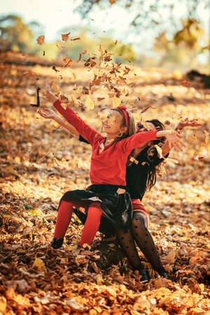 Beautiful young mother and her happy daughter having fun in the forest in sunset. They are laughing and little girl is throwing up  fallen leaves. 스톡 콘텐츠