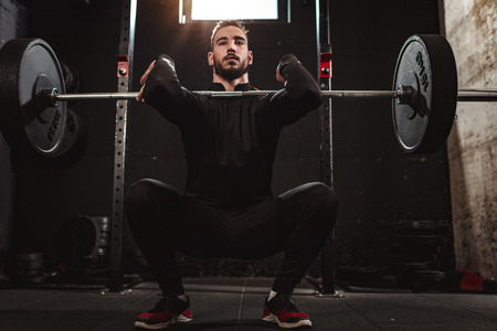 Young muscular handsome man is doing squat exercise with barbell at the gym.