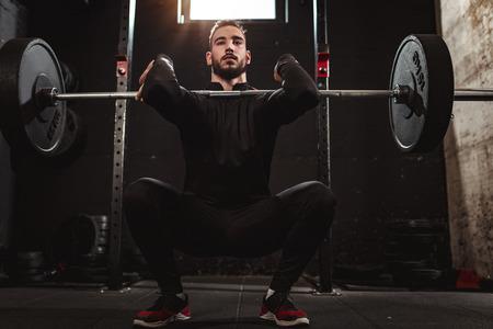 Joven guapo musculoso está haciendo ejercicio en cuclillas con barra en el gimnasio. Foto de archivo
