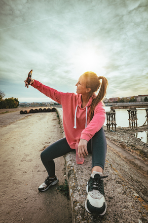 Young fitness woman is resting after hard training on the wall by the river bridge and taking selfie with smarthphone.