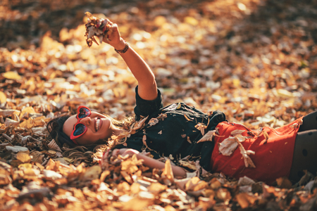 Beautiful young woman is enjoying in autumn  sunny forest colors. She is lying down on golden yellow leaves and having fun.
