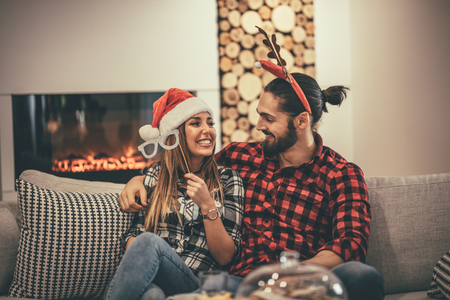 Cute beautiful couple is spending New Year eve at home sitting on sofa. They have great holidays having fun in nice company indoors.