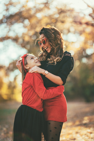 Beautiful young mother and her happy daughter having fun in the forest in sunset. They are hugging, smiling and looking each other.