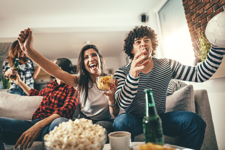 Friends are fans of sports games as football love spending their free time at home together. They are screaming and gesturing for a victory.