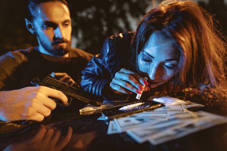 A criminal young woman drug addict sniffs a cocaine track with a rolled-up note.