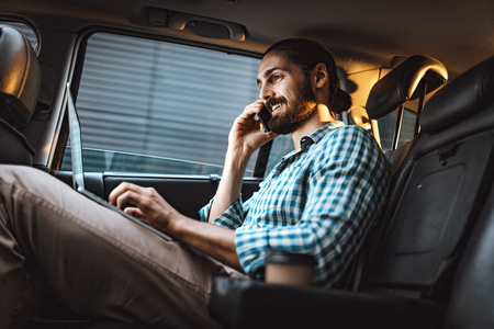 Young confident businessman is holding smartphone in his hand and texting on a laptop on the back seat in car.