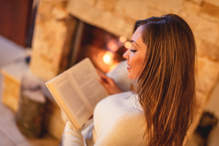Beautiful young smiling woman reading book and enjoying by the fireplace.