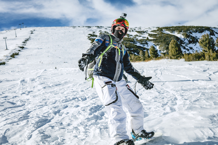 Young man rides snowboard and enjoying a frozen winter day on mountain slopes. Stock fotó