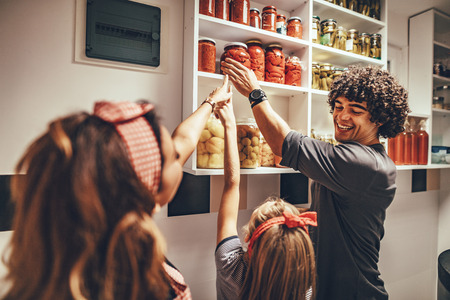 A happy family takes jars with pickled vegetables from the pantry shelf. Banco de Imagens