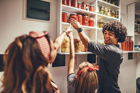 Una familia feliz saca frascos con verduras en escabeche del estante de la despensa.