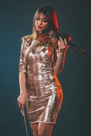Beautiful young smiling woman in sequin dress playing the classical music on violin.