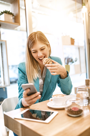 Young smiling businesswoman on a break in a cafe. He is having breakfast and using smartphone.