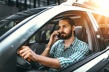 Man is holding smartphone in his hand and talking while driving a car.