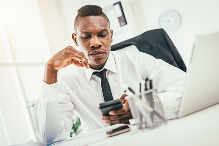 Pensive African businessman working on calculator in modern office and planning what to do next. Foto de archivo
