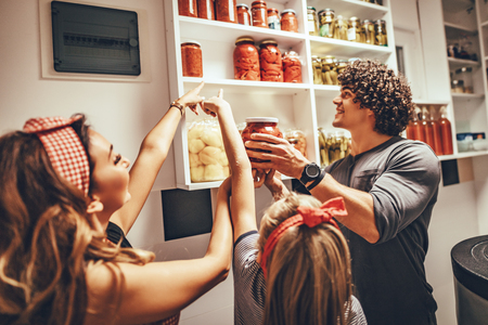 A happy family takes jars with pickled vegetables from the pantry shelf. Stock Photo