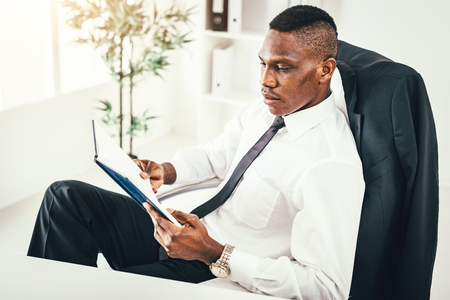 Pensive African businessman working in modern office and reading his notes in notebook and planning what to do next. Foto de archivo