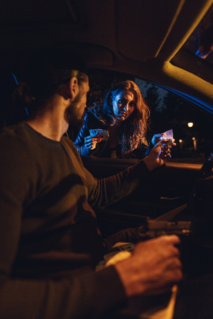The dealer sells a little bag of heroin or cocaine to a young woman from a car, and she gives him money.