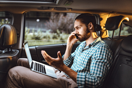 Young confident businessman is holding smartphone, talking and looking at laptop on the back seat in car.