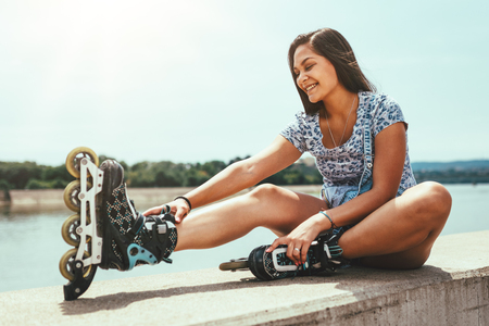 Young female skater is enjoying on the city river shore and ties her rollers on a beautiful summer day. Zdjęcie Seryjne