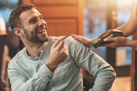 A handsome young man pays to waitress for coffee with credit card in a cafe. Stock Photo