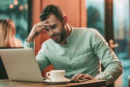 Attractive businessman using a laptop and thinking what is going wrong, while working in café.