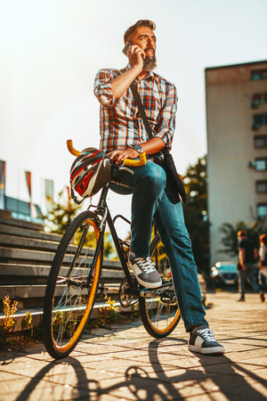 A handsome young man goes to the city with his bike, sitting on it, waiting for someone and talking oh smartphone.