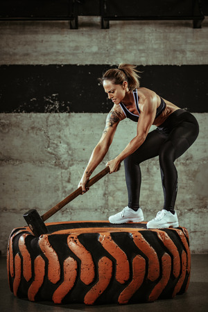 Young muscular woman hitting wheel tire with hammer on training at the gym. 写真素材