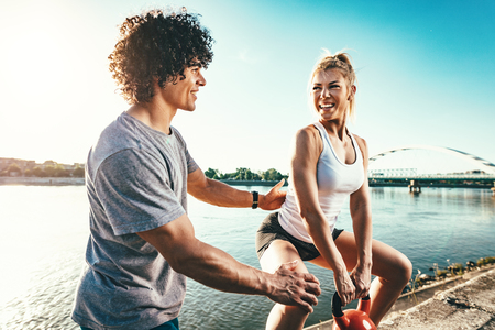 Young fitness couple is doing workout with kettlebell on the wall  by the river in a sunset. The woman is crouching and holding kettlebell, and the man supports her. Stock Photo
