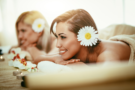Two cute young women are enjoying during a skin care treatment at a spa. Zdjęcie Seryjne