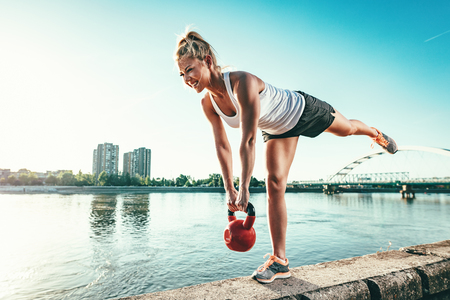 Young fitness woman is doing workout with kettlebell on the wall  by the river in a sunset.