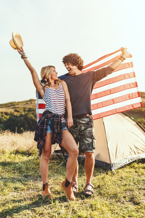 Happy young couple enjoys a sunny day in nature. They're hugging each other, holding an american flag in front a campsite tent.
