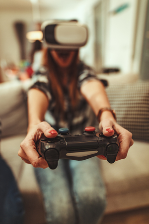 Happy young woman is playing video games with virtual reality glasses. She is having fun with new technology console online.