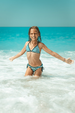 A little girl having fun in the waves of the sea and the drops of water are splashing all over her.