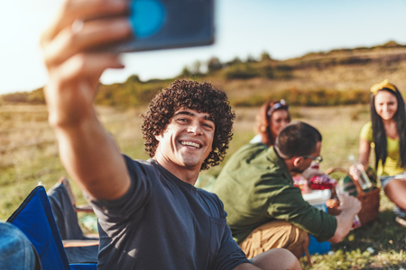Feliz joven disfruta de un buen día en la naturaleza. Él está sonriendo y tomando selfie con su teléfono inteligente.