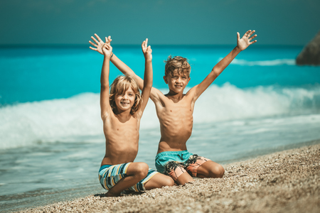 Two cute brothers are sitting on the beach and smiling looking at camera. Their arms are wide open.