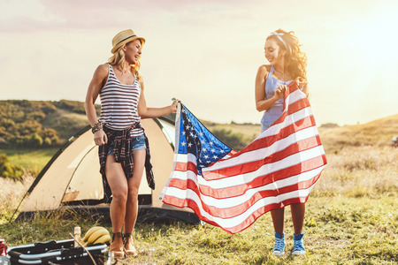 Happy young girl friends enjoys a sunny day in nature. Theyre holding an american flag in front a campsite tent. 版權商用圖片